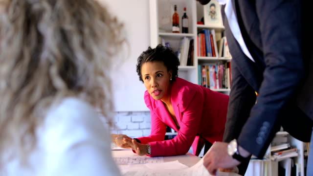 vídeos de stock e filmes b-roll de small group of architects.busy day at work.non-caucasian women leaders - grupo pequeno de pessoas