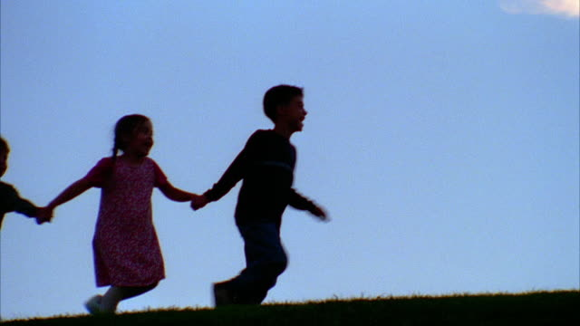A small group of children hold hands and run on a hilltop.