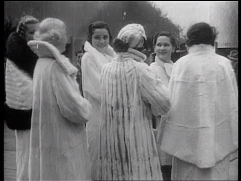 stockvideo's en b-roll-footage met b/w 1936 small group of female models modeling fur coats talking / rockefeller center, nyc - winterjas