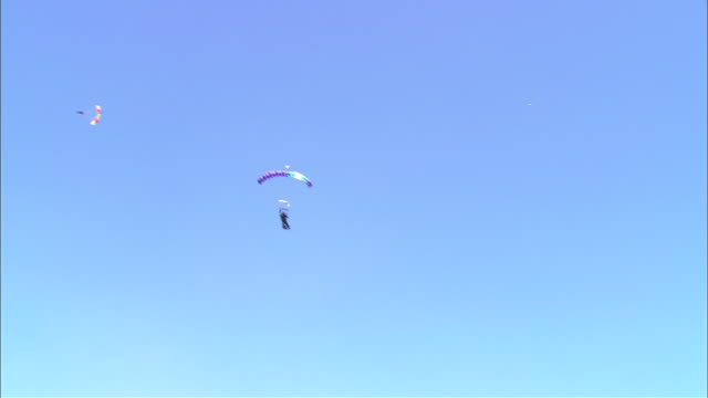 small group of hang gliders in air, one shown landing - hang gliding stock videos and b-roll footage