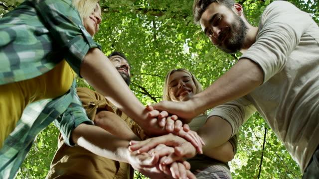 Petit groupe d'amis heureux, joignant les mains dans l'unité