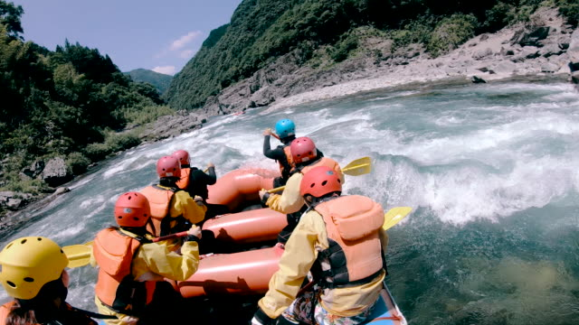 vídeos de stock e filmes b-roll de small group of men and women white water river rafting - lazer