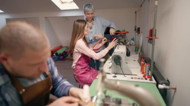piccolo gruppo di persone che lavorano sulle macchine da cucire in officina - aggiustare video stock e b–roll