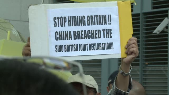 a small group of protesters gather outside hong kongs british consulate to accuse the former colonial power of failing to stop china from wielding... - occupy central stock videos & royalty-free footage