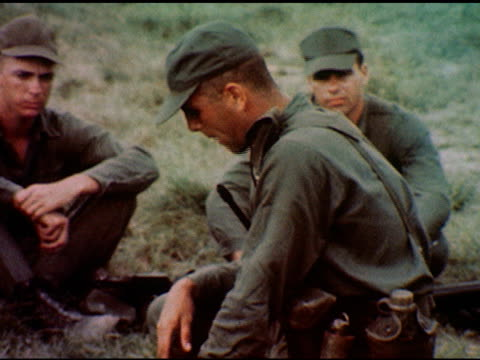 vídeos y material grabado en eventos de stock de / small group of soldiers sit in circle, slow zoom toward officer speaking in center / officer, soldier seated behind him prepares for military... - ropa de camuflaje