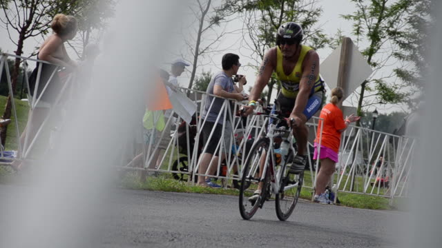 small group of spectators cheer on triathletes at the new jersey state triathlon at mercer county park in new jersey. - triatleta video stock e b–roll