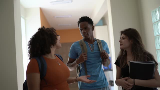 small group of students talking in the school / university corridor - community college stock videos & royalty-free footage