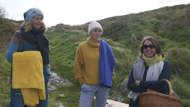 a small group of women swimmers stop for a chat on a coastal path getting ready for a swim in the sea. - 50 59 years stock videos & royalty-free footage