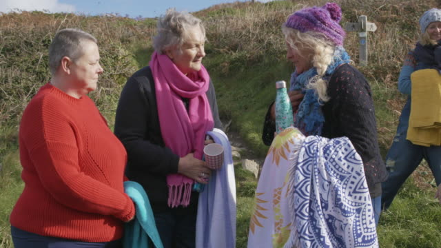 a small group of women swimmers stop for a chat on a coastal path getting ready for a swim in the sea. - retirement stock videos & royalty-free footage