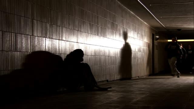 vídeos y material grabado en eventos de stock de a small group of young men run and jump through a  tunnel where a homeless person crouches and sleeps. - sin techo