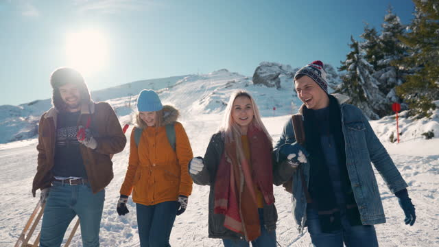 small group of young people smiling and talking while going down the snowy mountain - warm clothing stock videos & royalty-free footage
