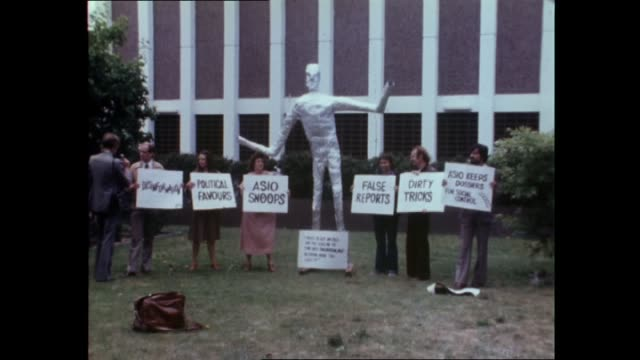 """stockvideo's en b-roll-footage met small group with alien looking sculpture, holding up signs, """"i tried to get my file, and they asked me to come back tomorrow, but i'm staying here... - media interview"""