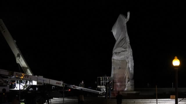 small groups of people gather around the area where a statue of christopher columbus is wrapped and removed in chicago - absence stock videos & royalty-free footage