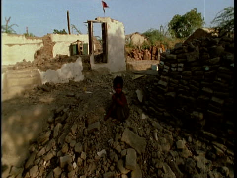 vidéos et rushes de ms small gujarat, indian boy sitting amongst ruins of house, gujarat, india - orphelin
