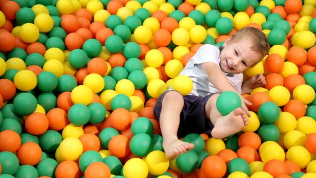 Small happy boy romps in multicolored balls