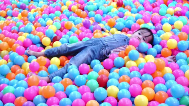 small happy female romps in multi colored balls - softness stock videos & royalty-free footage