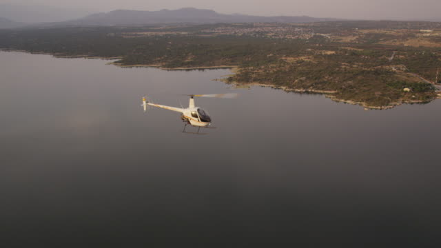 ms small helicopter flying over lake in semi-arid landscape, air-to-air view, red r3d 4k - red lake stock videos & royalty-free footage