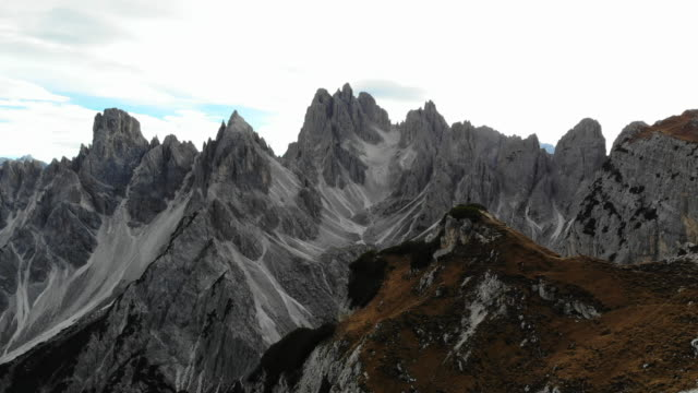 vidéos et rushes de small hiker facing the sharp dolomite mountains in the italian alps from top of a hill. - vertige