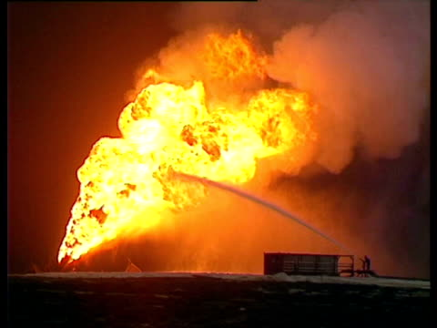 small hose of water hitting large flames. gulf war: kuwait, 1991. - 1991 stock videos and b-roll footage