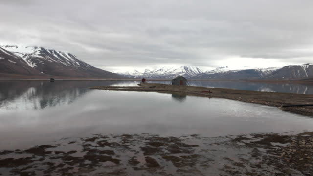 a small house on a tiny peninsula on an arctic lake in sumer time; beautiful mountains. covered by snow in the back; a car driving on an empty road, spitsbergen, svalbard archipelago - north stock videos & royalty-free footage