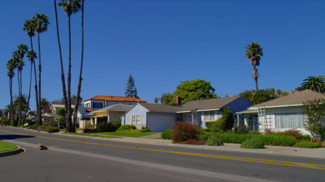 WIDE PAN small houses on suburban street with palm trees, cars pass, Santa Barbara, California