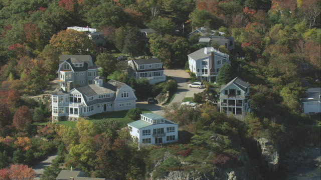 aerial small inns and rental cottages nestled among fall foliage on bluff overlooking the shore / ogunquit, maine, united states - 闊銀幕 個影片檔及 b 捲影像