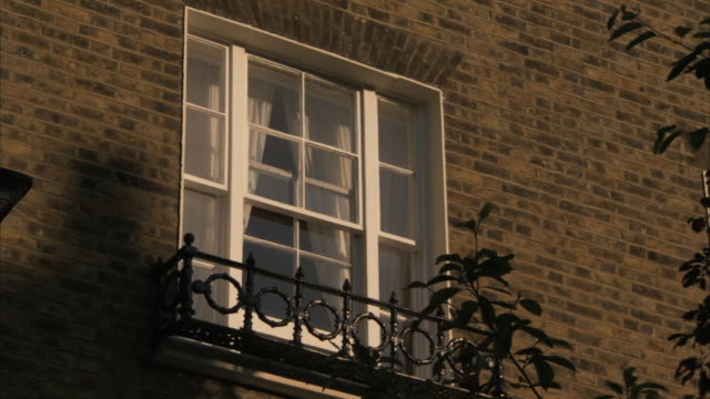 A small iron balcony before window of brick building. Available in HD.