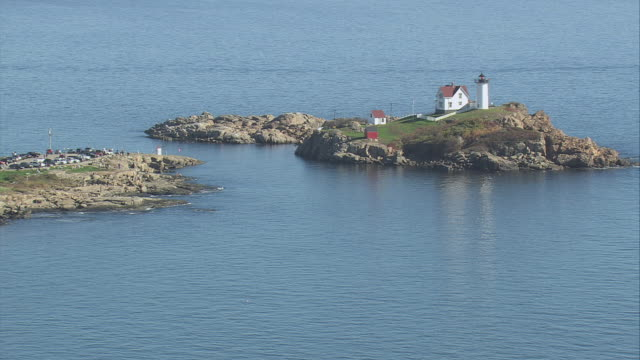 aerial small island with cottage and lighthouse on bluff / york, maine, united states - island stock videos & royalty-free footage
