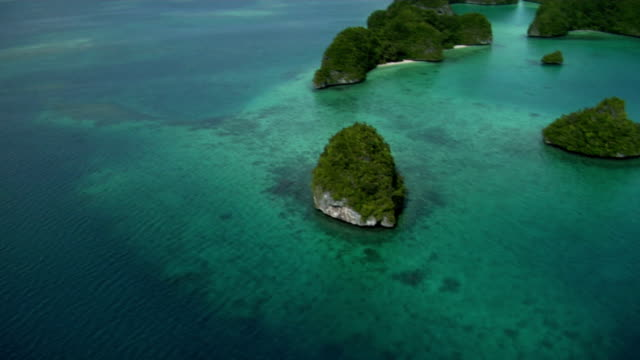 Small islands are surrounded by reefs and turquoise water. Available in HD.