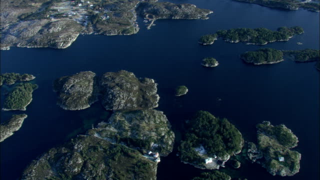 Small islands dot an ocean inlet in Norway. Available in HD.