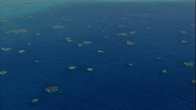 Small islands of coral in the blue water of the Coral Sea. Available in HD.