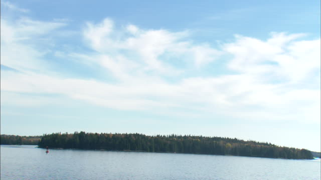 small islands w/ trees on penobscot bay blue waters bottom of frame some unidentifiable boats bg partial cloudy blue sky bg - augusta maine stock videos & royalty-free footage