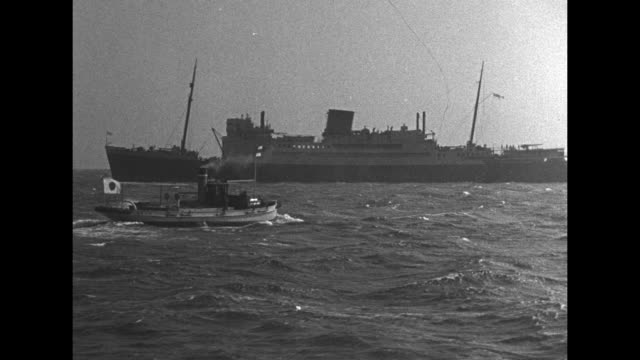 small japanese boat with japanese flag flying moves across choppy waters toward british auxiliary cruiser kanimbla during world war ii / japanese... - 囚人点の映像素材/bロール