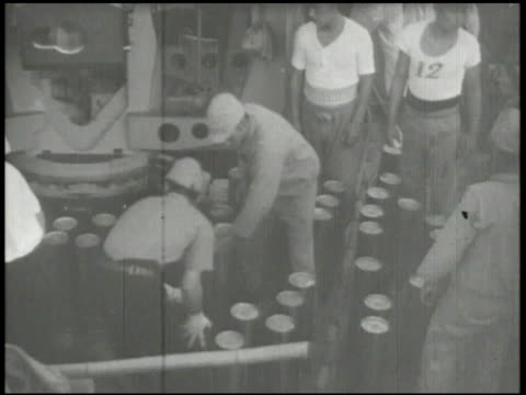 Small Japanese cargo ship docking w/ another ship Imperial Japanese Navy sailors loading unloading stocking shells World War II WWII Pacific Front...