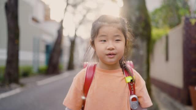 住宅街の桜桜の木の下で歩いて学校に歩く小さな日本の女子高生 - 初登校日点の映像素材/bロール
