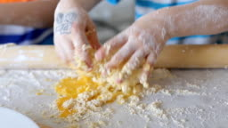 Small kids make dough. Children play in the kitchen and get dirty in flour