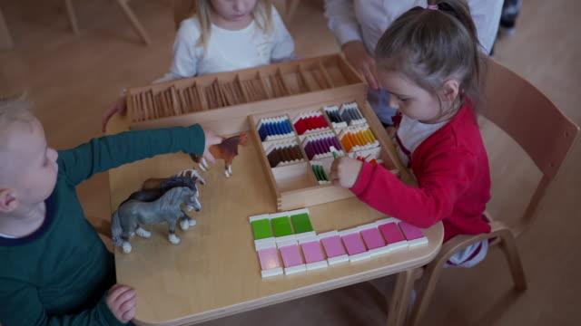 vídeos de stock e filmes b-roll de small kids playing with toys in kindergarten classroom - edifício de infantário
