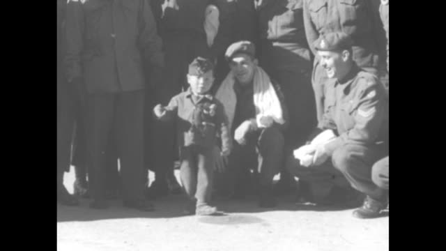 mcu small korean boy in military uniform about faces as canadian soldiers look on / cu boy salutes / cu two canadian soldiers smile / cu canadian... - military uniform stock videos and b-roll footage