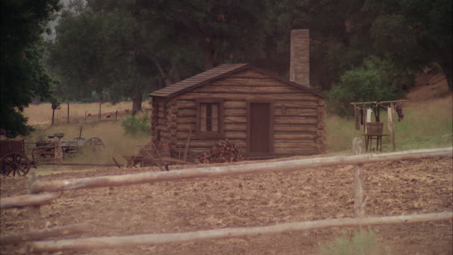 ms small log cabin near farm field / unspecified - log cabin stock videos & royalty-free footage
