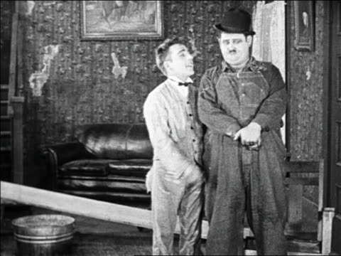 b/w 1925 small man kissing fat man on cheek they hug / feature - oliver hardy stock videos & royalty-free footage