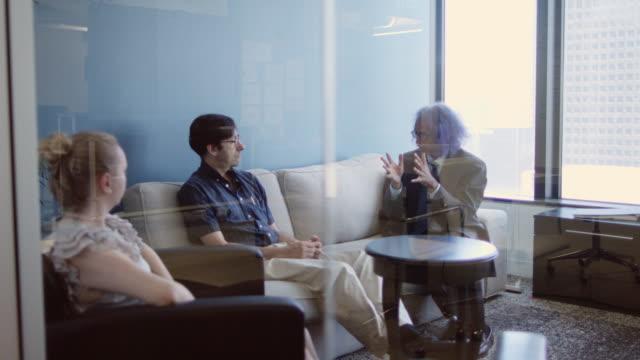 stockvideo's en b-roll-footage met kleine vergadering gezien door glas - men