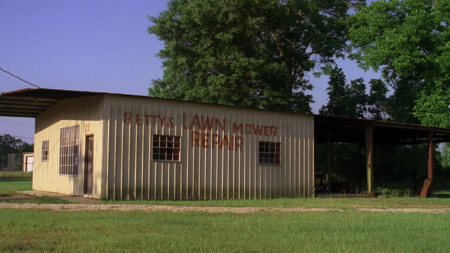 ms small metal utility building and shed. sign on side bettys lawn mower repair - western script stock videos & royalty-free footage