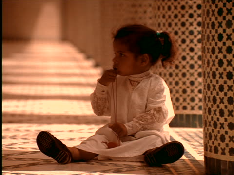 vidéos et rushes de portrait small middle eastern girl sitting on floor of mosque chewing on piece of string / morocco - seulement des petites filles