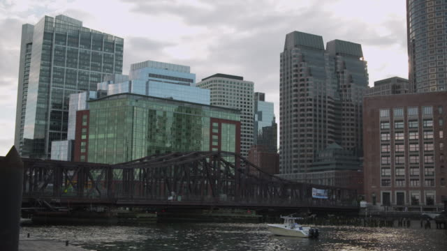 a small motor boat bobs on the fort point channel in front of the old northern bridge and modern office buildings, boston, massachusetts, usa. - boston massachusetts stock videos & royalty-free footage