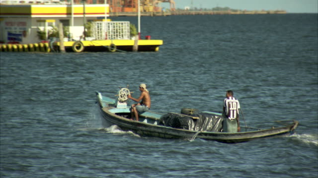 A small motorboat cruises through the water near a harbour. Available in HD.