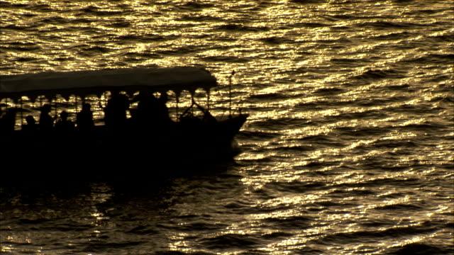 vídeos de stock, filmes e b-roll de a small motorboat takes passengers across lake pichola at sunset. - passear sem destino
