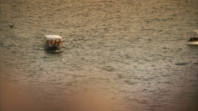 A small motorboat takes passengers across Lake Pichola in Udaipur, India.