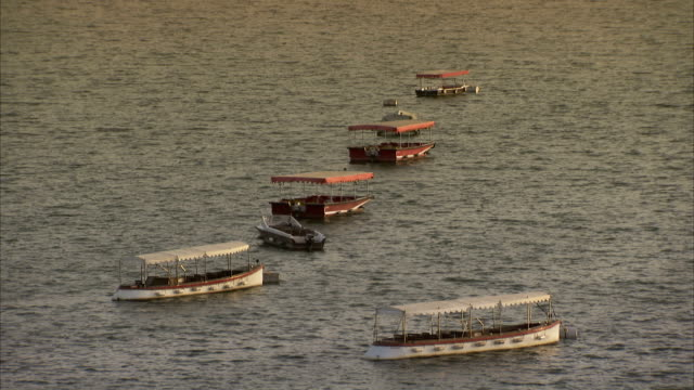 vídeos de stock, filmes e b-roll de small motorboats at anchor on lake pichola, udaipur. - ancorado