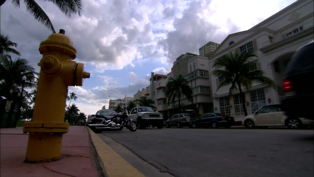 a small motorcycle weaves its way through south beach street traffic in miami. - rinnsteinkante stock-videos und b-roll-filmmaterial