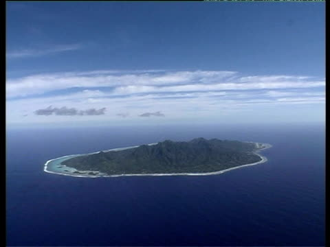 Small mountainous Rarotonga island surrounded by coastline and clear blue sea Cook Islands